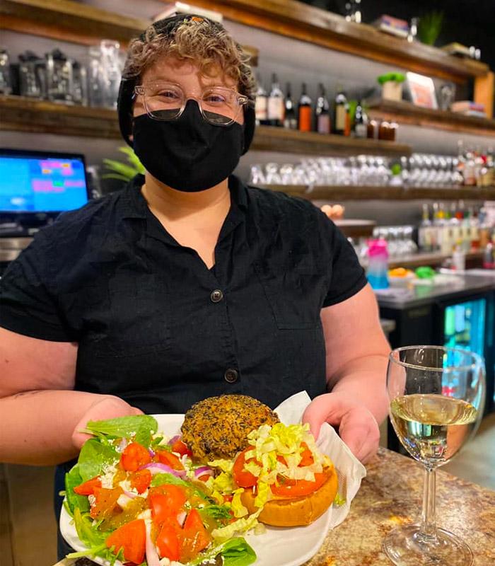 JavaVino Server Holding a Black Bean Burger with a Side Salad.