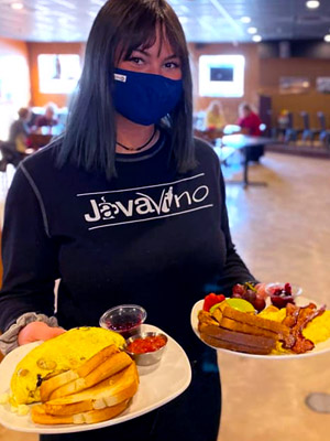JavaVino Server Holding Plated Omelettes with a Side of Toast and Jam.